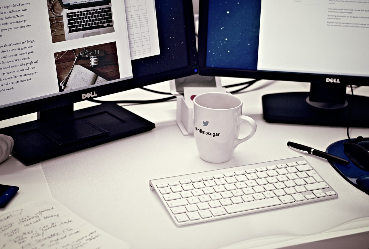 Photo of two screens in front of a keyboard, with a mug of coffee also on the table